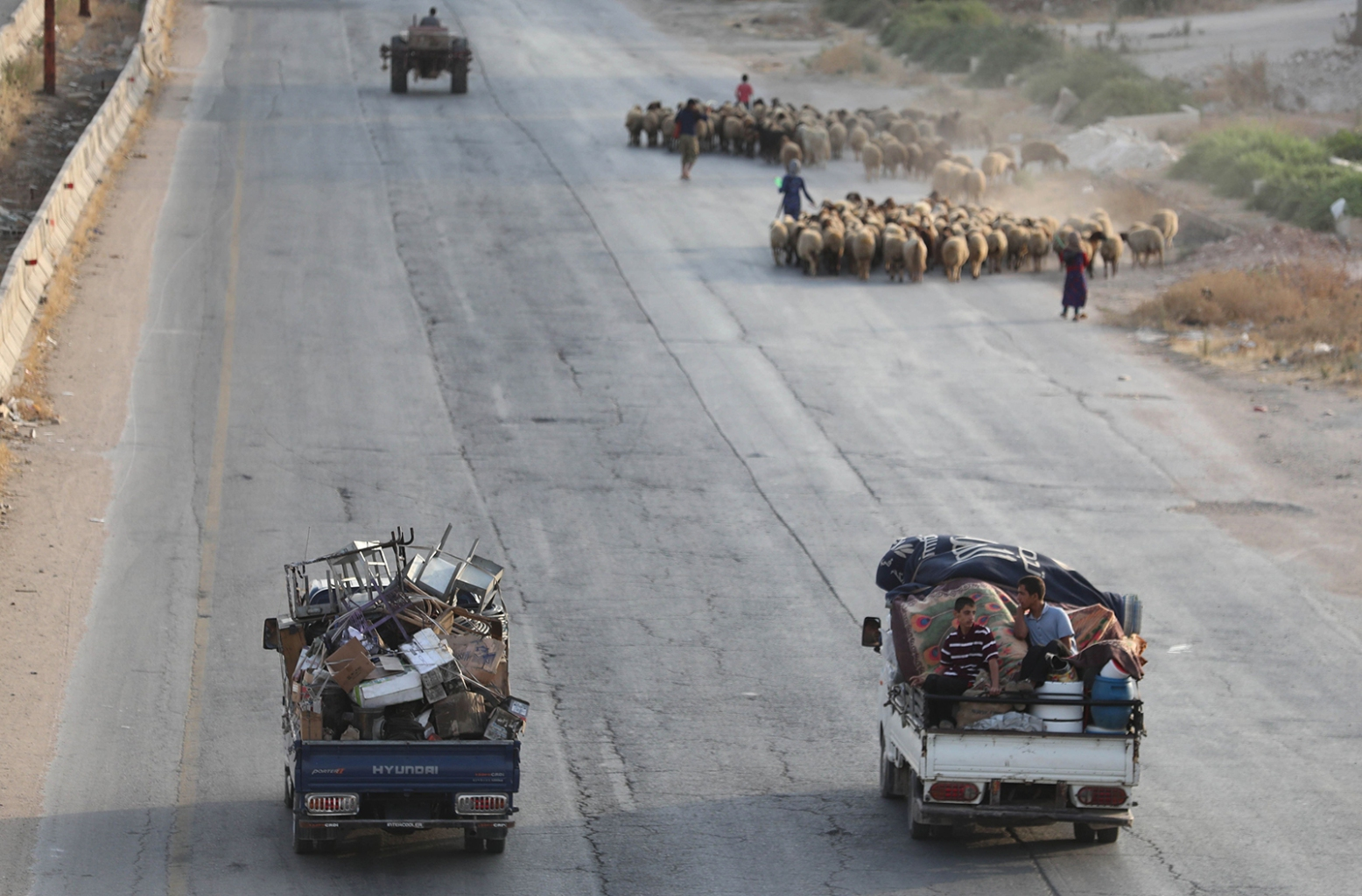 Syrian families from the southeastern Idlib province and the northern countryside of Hama flee battles in trucks loaded with their belongings past a flock of sheep on the highway near Maaret al-Numan on Aug. 14. OMAR HAJ KADOUR/AFP/Getty Images
