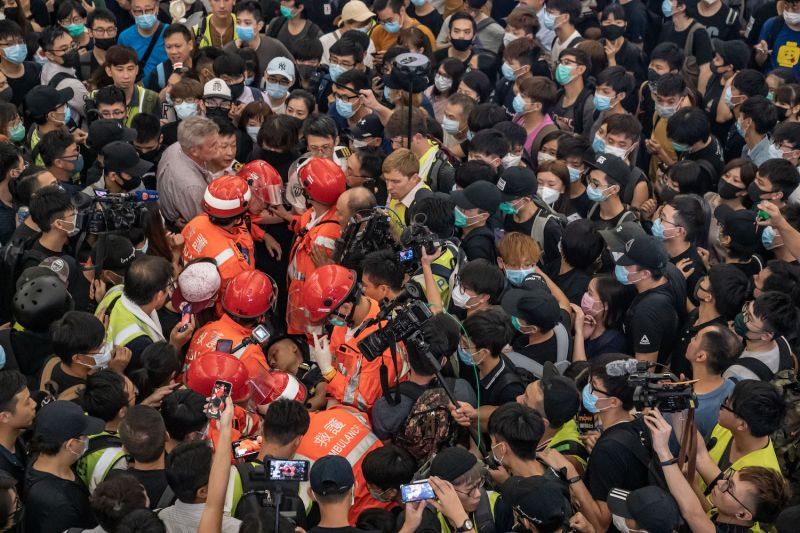 Paramedics remove an injured man suspected of being an undercover police officer and attacked during a protest at Hong Kong International Airport during a demonstration on Aug. 13.