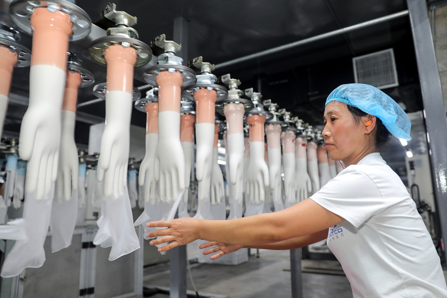 An employee works on a medical glove production line at a factory in Huaibei in China's eastern Anhui province on Aug. 14. STR/AFP/Getty Images