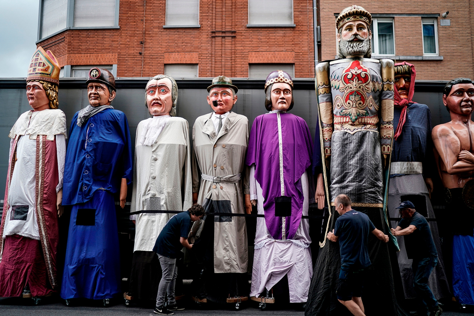 "Members of the group ""The Carriers of the Giants of the Province of Liege"" prepare giant puppets for a folk parade in Outremeuse, Liege, Belgium, on August 15 during Assumption Day celebrations. KENZO TRIBOUILLARD/AFP/Getty Images"