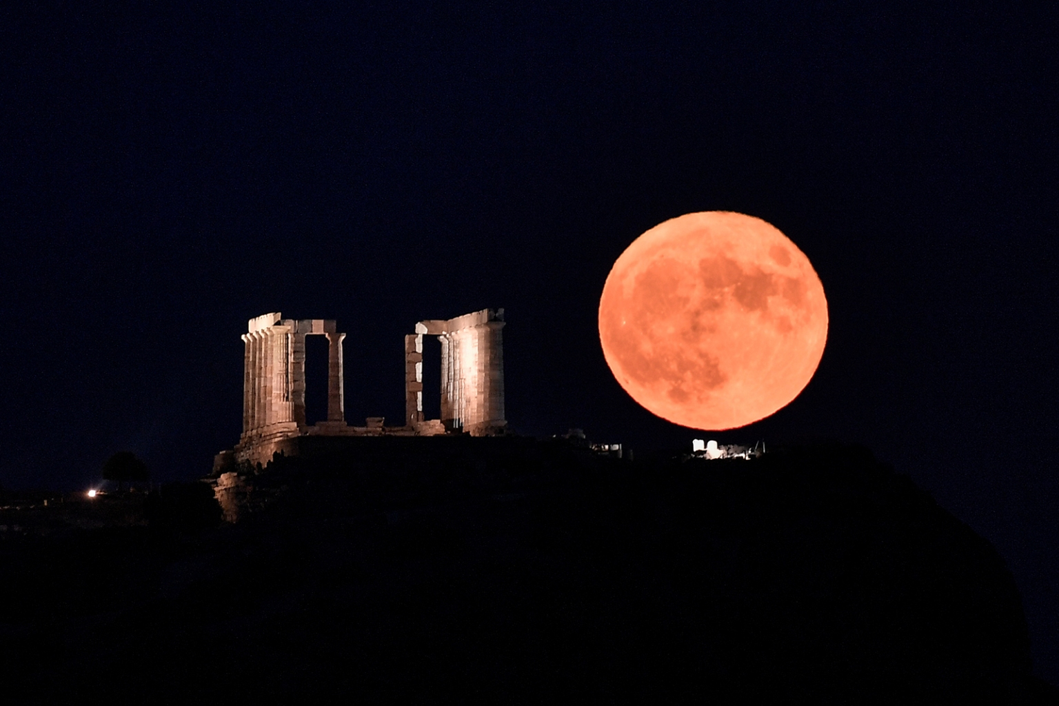The full moon rises next to the Poseidon Temple at the Cape of Sounion, south of Athens, on Aug. 15. LOUISA GOULIAMAKI/AFP/Getty Images