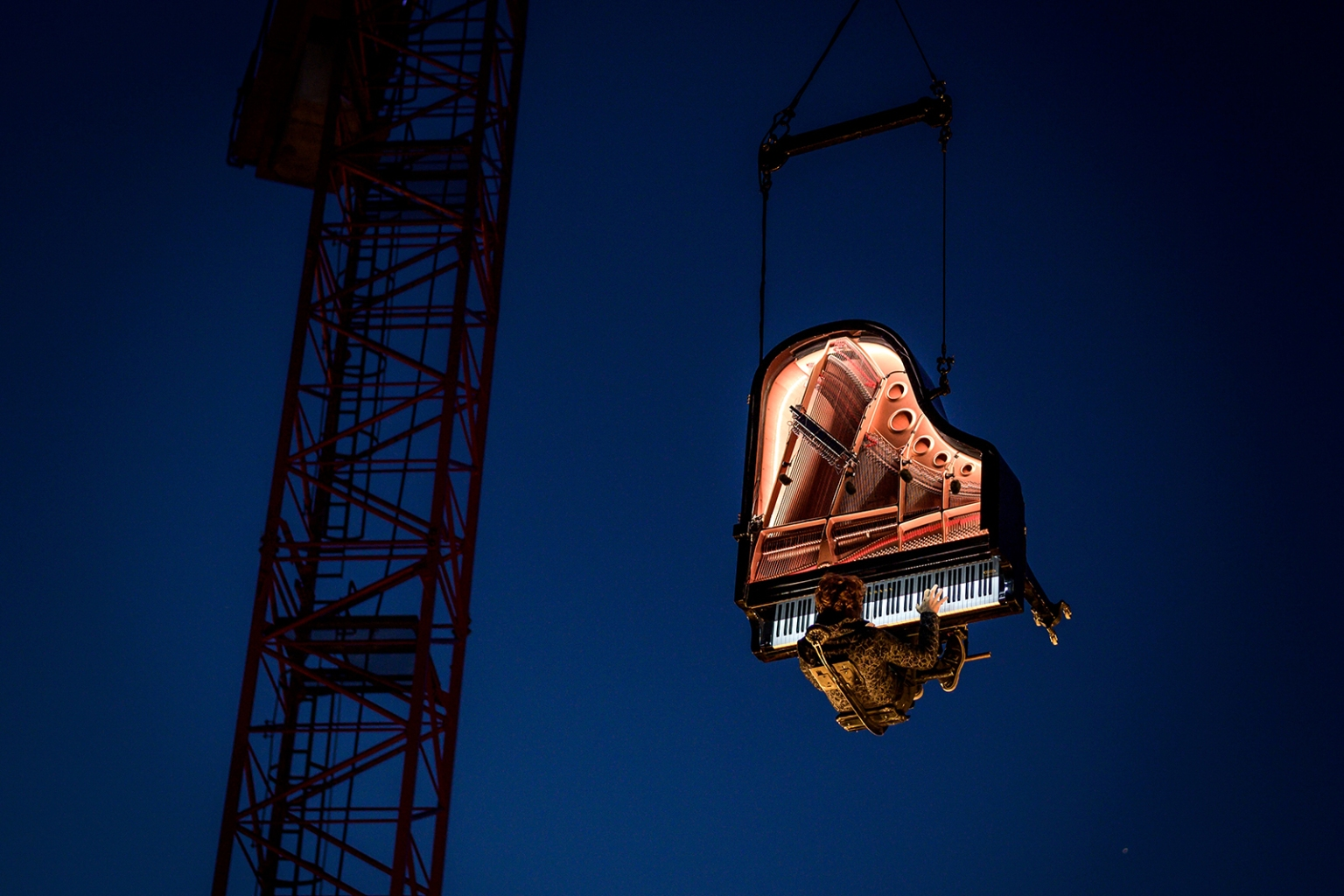 "Swiss pianist and composer Alain Roche performs Chantier suspended in the air with his grand piano from crane on Aug. 16 during the 20th ""Jeux du Castrum"" a multidisciplinary festival in Yverdon-les-Bains. FABRICE COFFRINI/AFP/Getty Images"