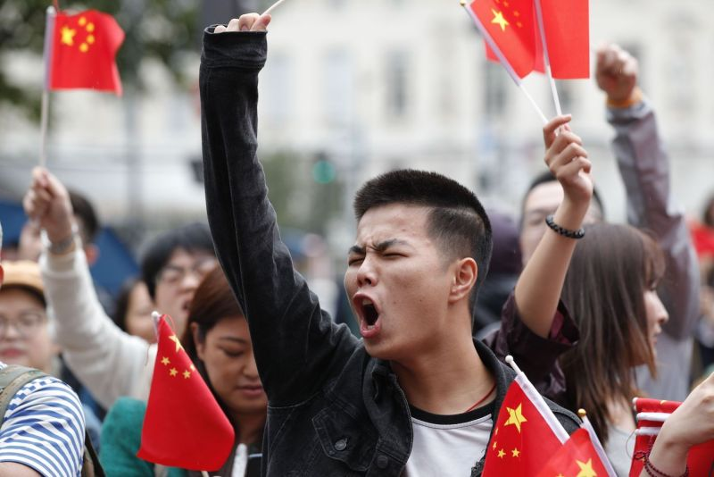 Counter-protesters wave Chinese flags in the Place Saint Michel, central Paris, as they oppose demonstrators gathering to support  protests in Hong Kong, on August 17, 2019.