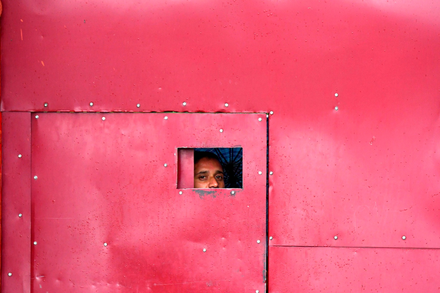 A worker looks through the gate of a closed school in Srinagar in Jammu and Kashmir on Aug. 19. PUNIT PARANJPE/AFP/Getty Images
