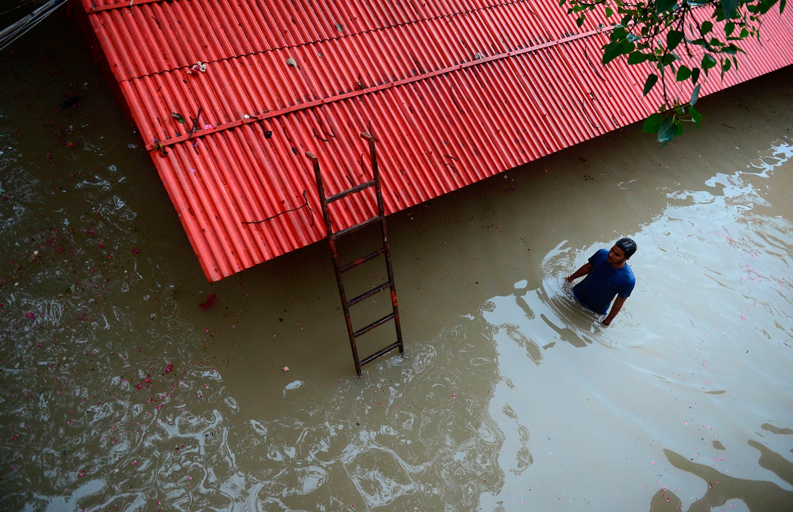 A priest walks inside the submerged Hanuman temple near Sangam following heavy rains in Allahabad, India, on Aug. 19. SANJAY KANOJIA/AFP/Getty Images