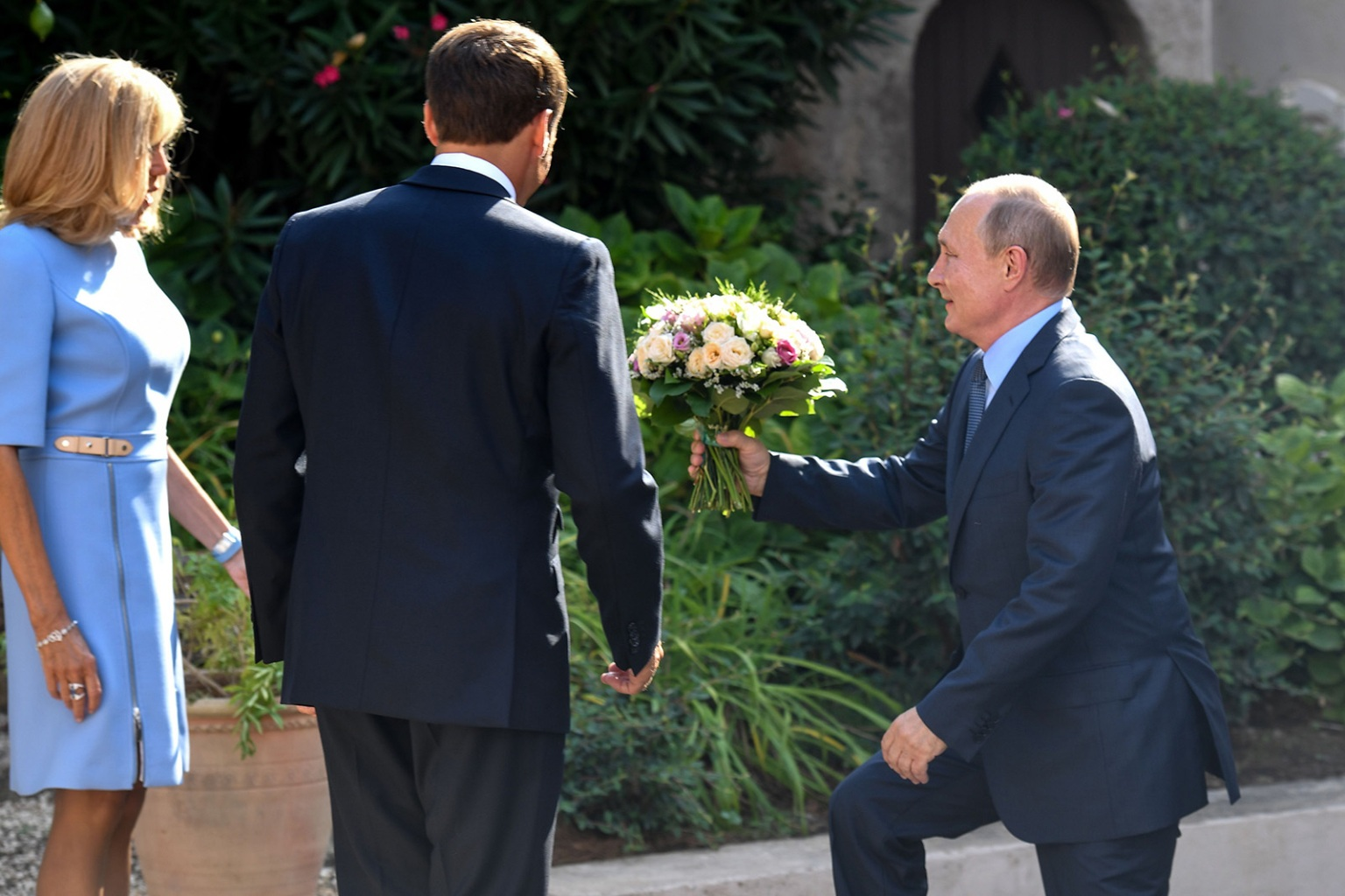 Russia's President Vladimir Putin, flanked by French President Emmanuel Macron, gives flowers to Brigitte Macron at the French president's summer retreat on the Mediterranean coast in southern France on Aug. 19. GERARD JULIEN/AFP/Getty Images
