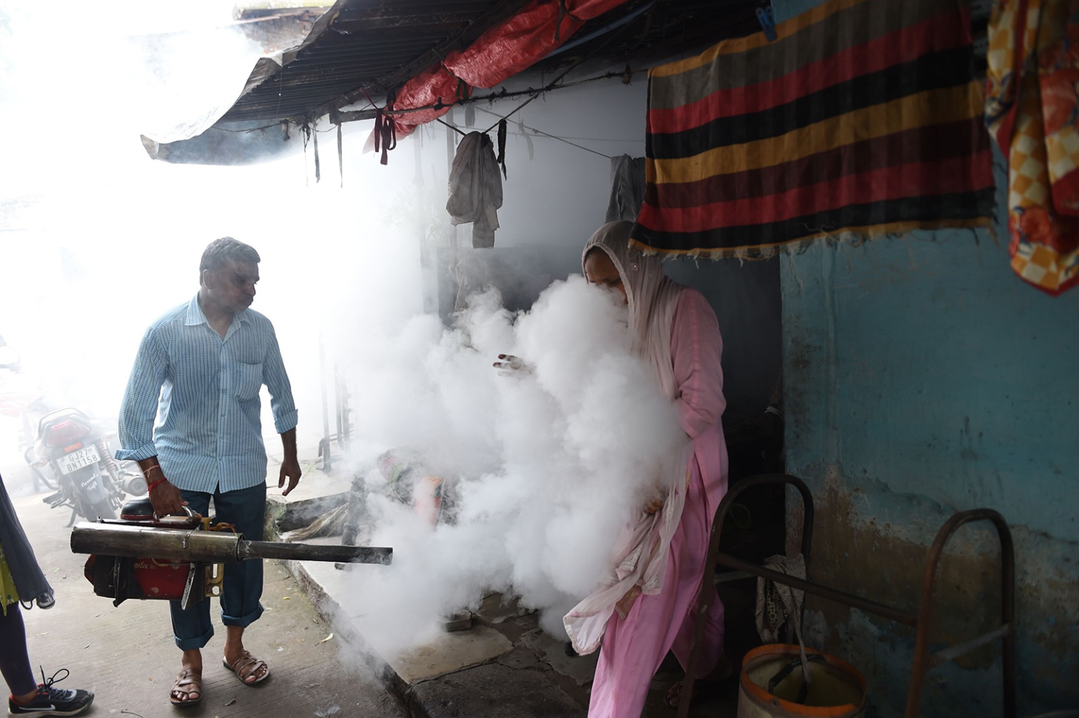 A worker fumigates an area to prevent mosquitos from breeding in a residential colony during World Mosquito Day in Ahmedabad on Aug. 20. SAM PANTHAKY/AFP/Getty Images