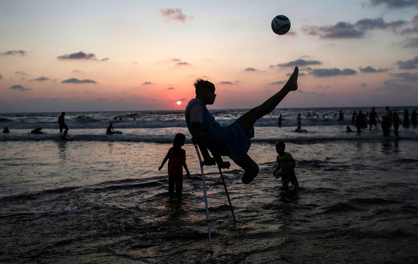 Palestinian Mohammed Eliwa, 17, who lost his leg during clashes on the border with Israel, plays football on the beach in Gaza City on Aug. 20. MAHMUD HAMS/AFP/Getty Images