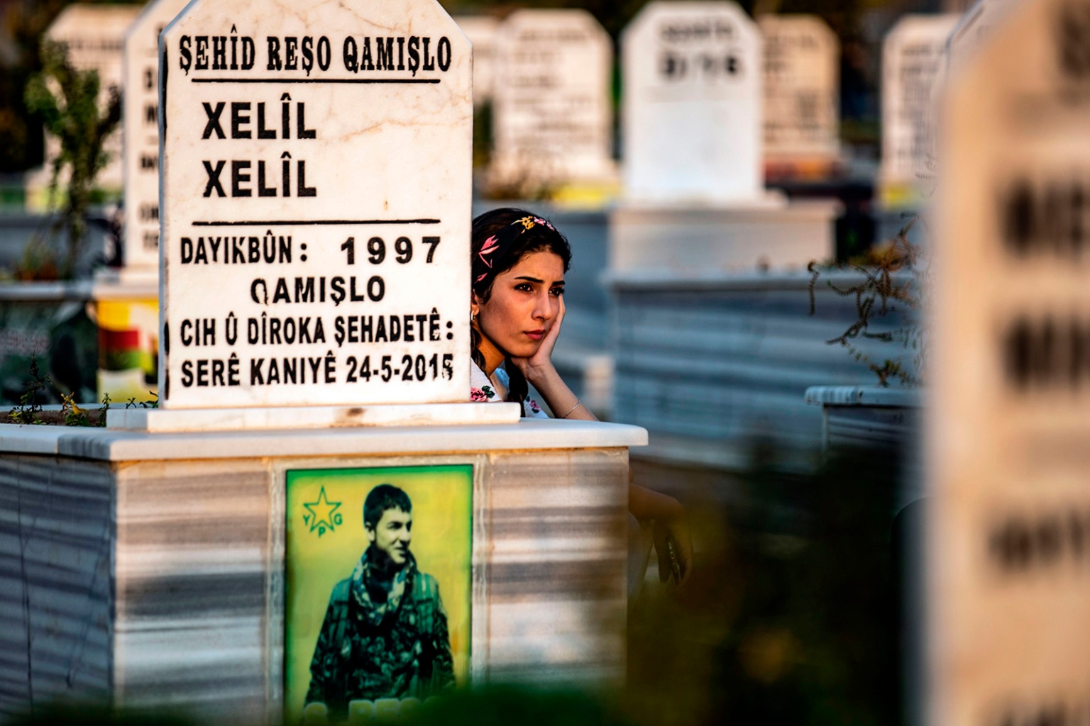 A Kurdish woman visits the grave of a relative during a funeral for a member of the Kurdish Internal Security Police Force in the northeastern Syrian Kurdish-majority city of Qamishli on Aug. 20. DELIL SOULEIMAN/AFP/Getty Images