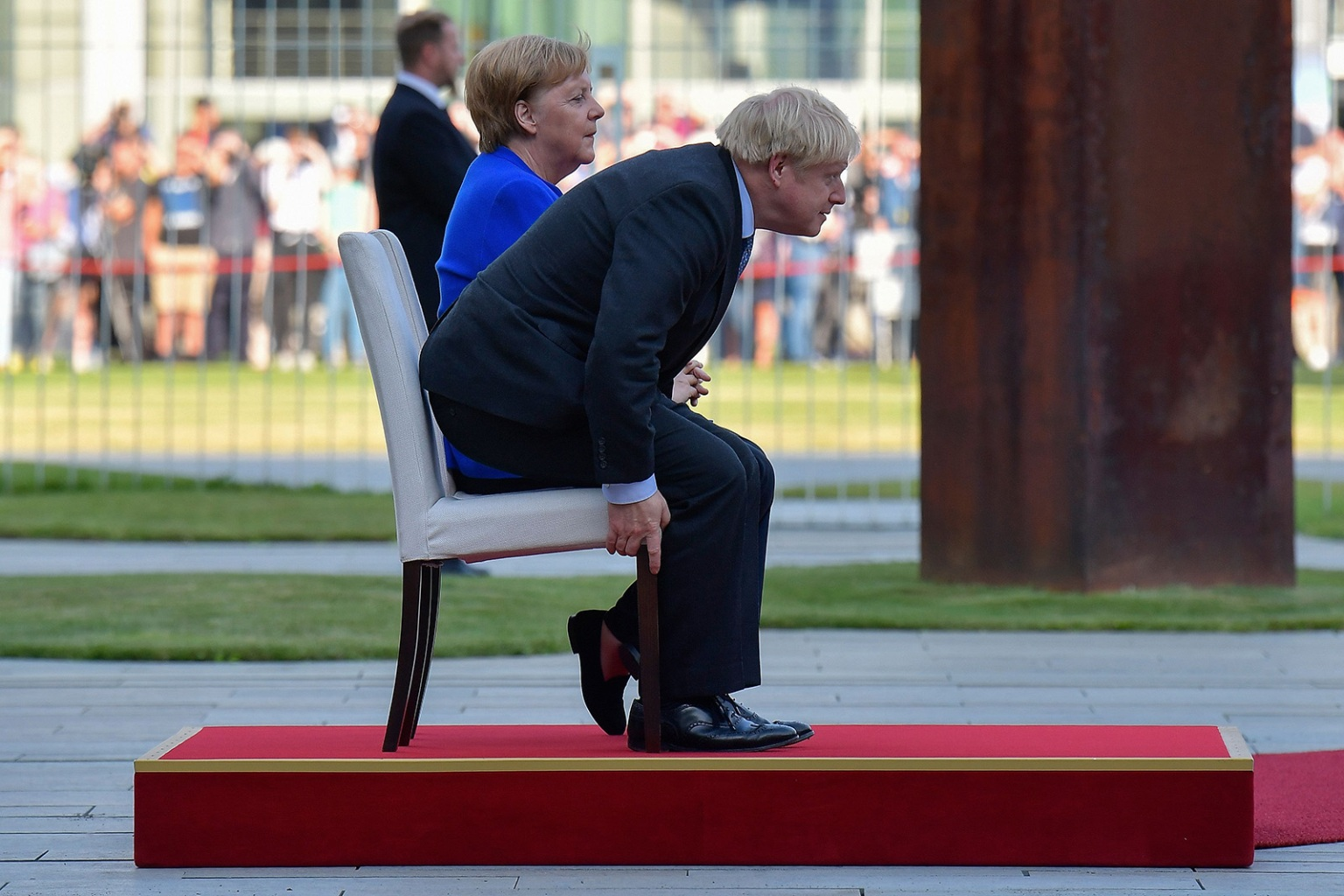 German Chancellor Angela Merkel and British Prime Minister Boris Johnson sit for the national anthems during a ceremony with military honors at the Chancellery on his first foreign visit since taking office in Berlin on Aug. 21. TOBIAS SCHWARZ/AFP/Getty Images