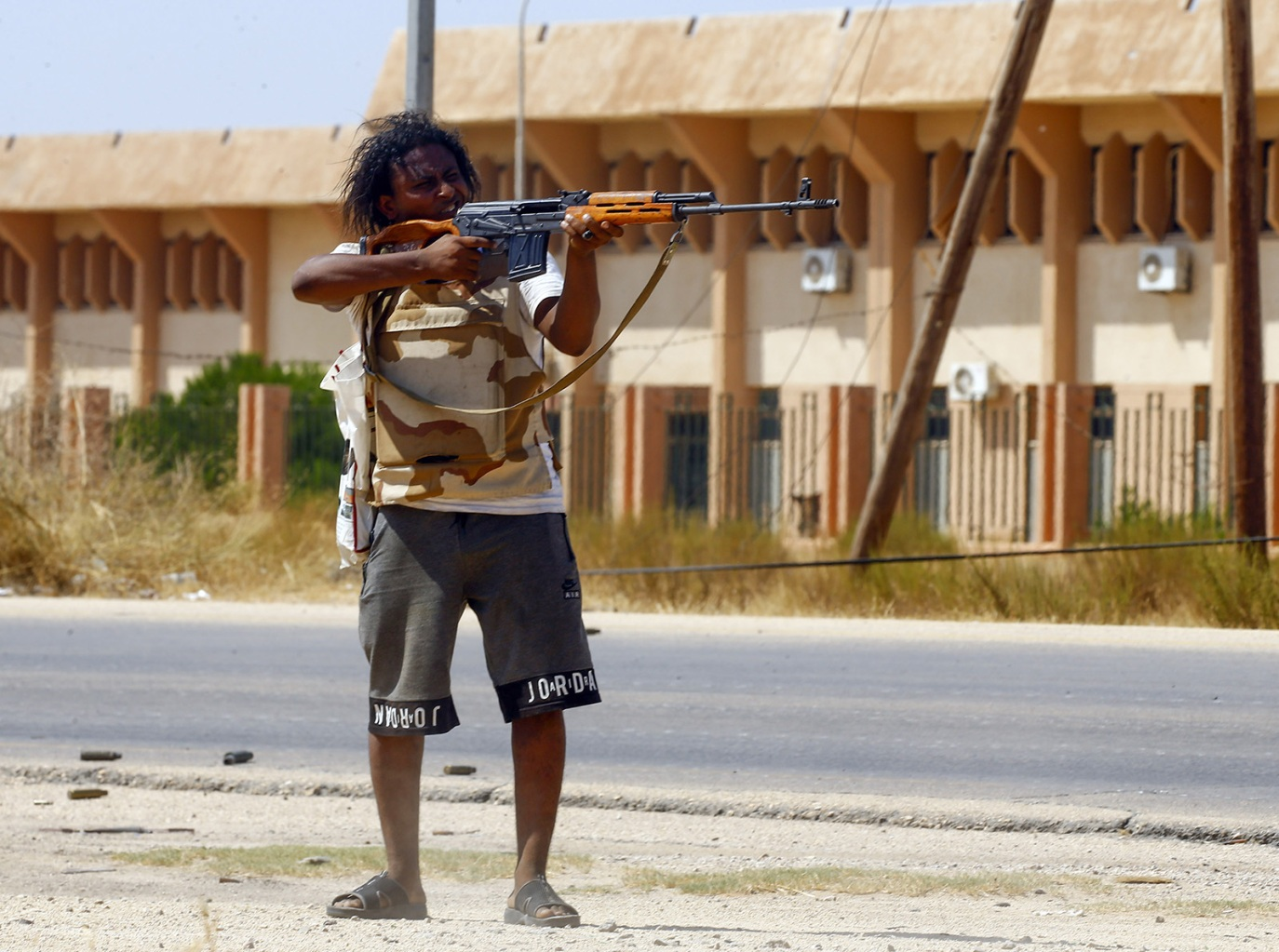 A fighter loyal to the U.N.-recognized Government of National Accord points his gun toward enemy lines during clashes with forces loyal to strongman Khalifa Haftar, in Espiaa, Libya, on Aug. 21. MAHMUD TURKIA/AFP/Getty Images