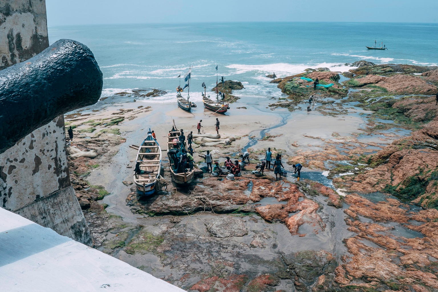 "Fishermen tend to their boats on the shores of Cape Coast Castle on Aug. 18. African-American visitors are flocking to Ghana as it marks the ""Year of Return"" to remember the 400th anniversary of the first slave ship landing in Virginia. NATALIJA GORMALOVA/AFP/Getty Images"