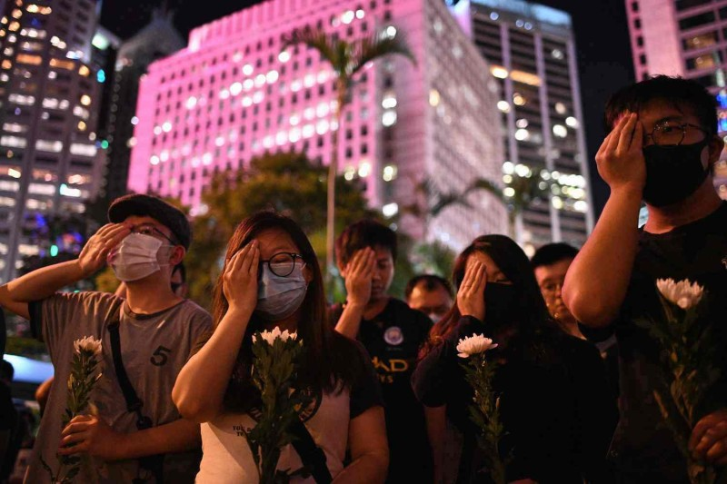 Protesters cover their right eyes as they gather in Hong Kong on Aug. 30.