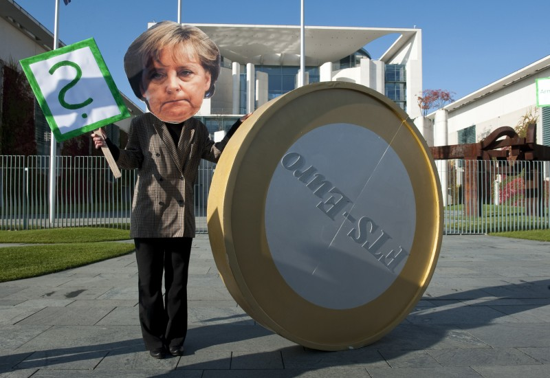 A protester dressed as German Chancellor Angela Merkel stands next to a giant 1 Euro coin during a demonstration in front of the chancellery in Berlin October 21, 2011, calling on Germany and France to spend more on alleviating poverty and protecting the environment, rather than on banks.