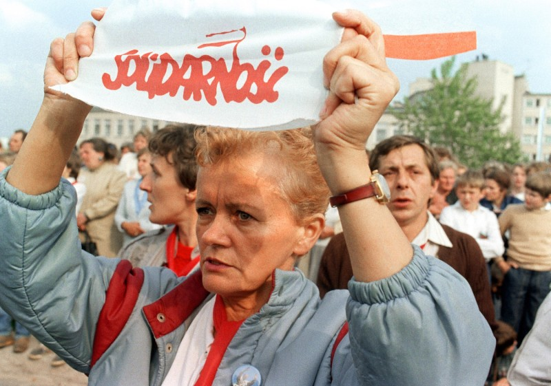 "A Solidarity union supporter holds a banner reading ""Solidarnosc"" as she and several thousands of people gather for an open-air mass celebrated by Pope John Paul II in Gdansk on June, 12 1987."
