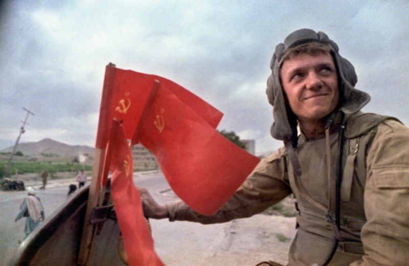 A soldier atop an armored personal vehicle smiles as Soviet troops stop in Kabul prior to their withdrawal from Afghanistan on May 16, 1988.