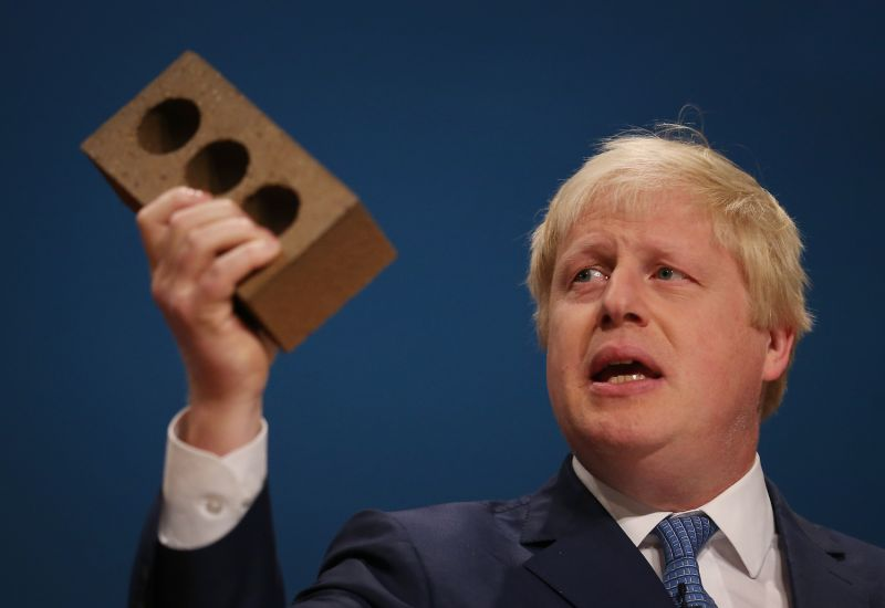 Then-London Mayor Boris Johnson holds a brick aloft as he addresses the Conservative Party conference in Birmingham, England, on Sept. 30, 2014.