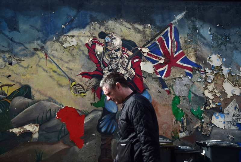A man walks past a mural marking unionist territory in Londonderry, Northern Ireland, on May 4, 2016.