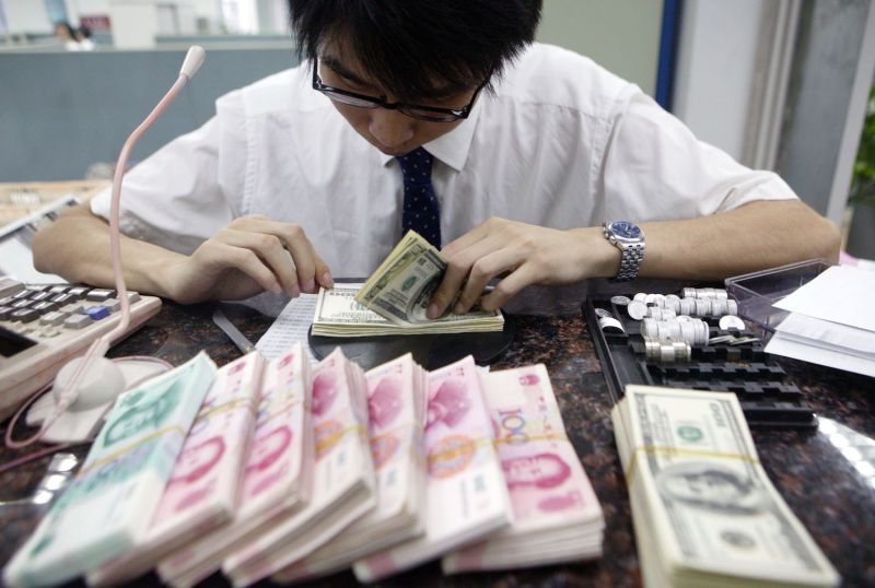 A clerk counts stacks of Chinese yuan and U.S. dollars at a bank in Shanghai on July 22, 2005.
