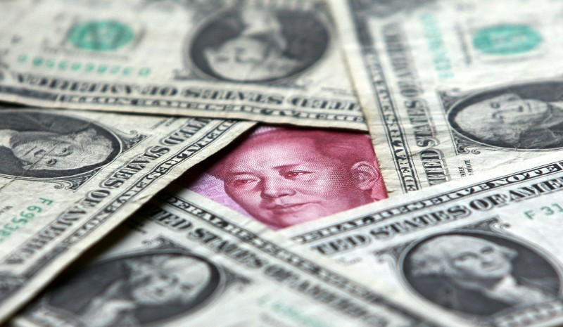 Dollars and yuan notes are seen at a bank on May 15, 2006 in Beijing, China.