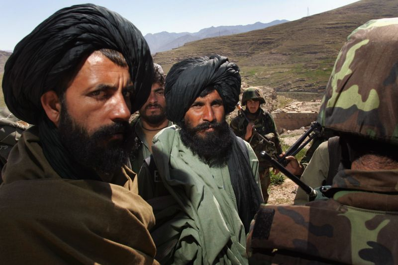 Local Afghan militia and Afghan Army soldiers consult March 14, 2007 in Kajaki, Helmand province, Afghanistan. Afghan troops, along with British Marine trainers, patrol through the area near the Kajaki hydroelectric dam.
