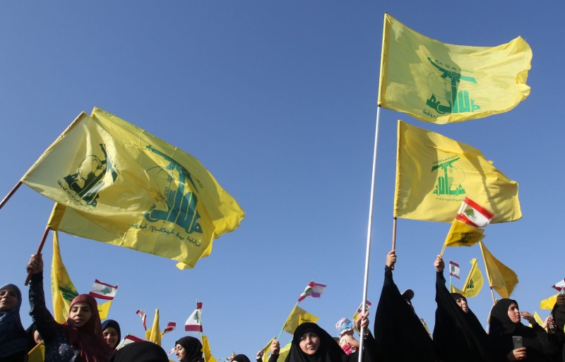 Supporters of Hezbollah fly the group's flag during an event marking the 11th anniversary of the end of the 2006 war with Israel in the village of Khiam in southern Lebanon on Aug. 13, 2017.