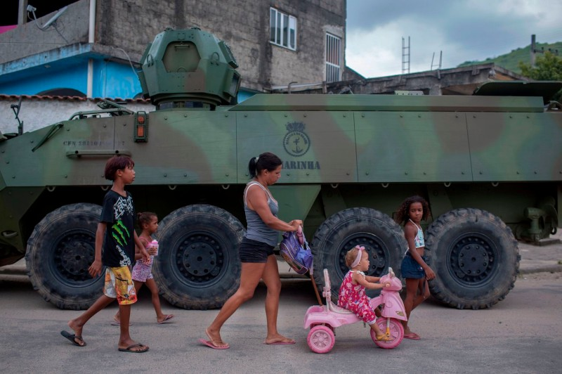 A woman and children walk past an armored vehicle in Rio de Janeiro on March 7, 2018.