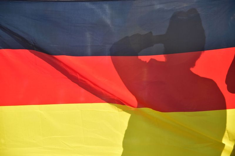 A person is silhouetted behind the German national flag in Berlin on June 27, 2018.