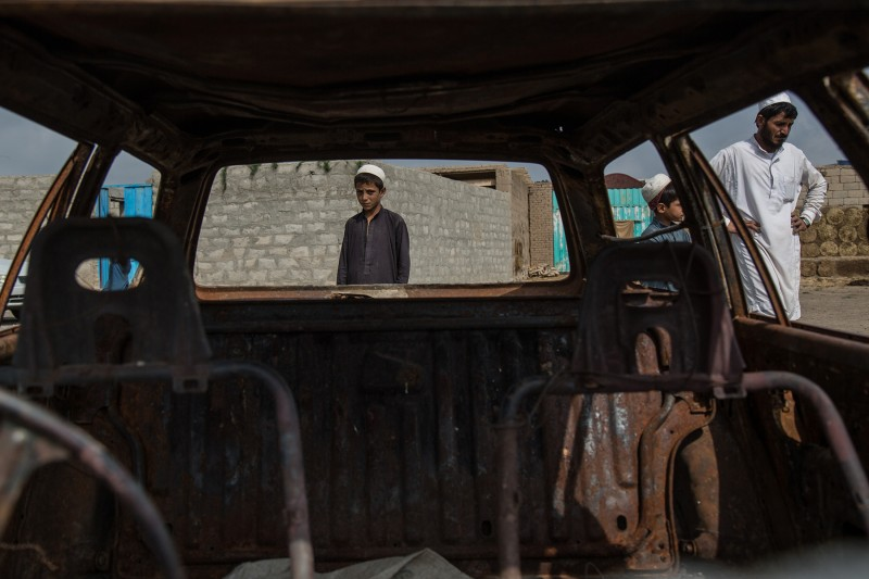 Afghan villagers are framed in the broken windows of Noor Walli Khan's car, burned during a Khost Protection Force raid in Tani district, Khost province, on July 28. Gul Rahim, 7, left, says he has trouble sleeping at night, hearing the helicopters and drones fly over his house.