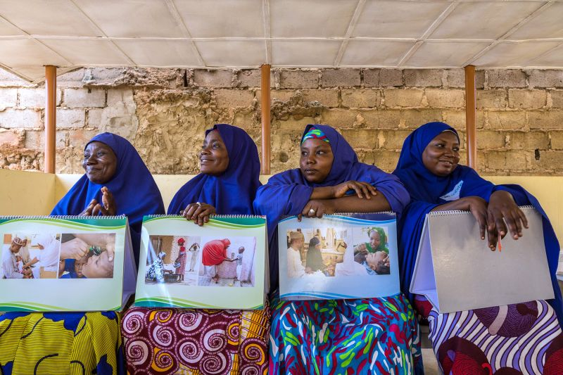 Volunteer community mobilizers (VCMs) hold flip charts used for educating parents about polio and other routine immunizations at a health center in Kano, Nigeria, on July 23.