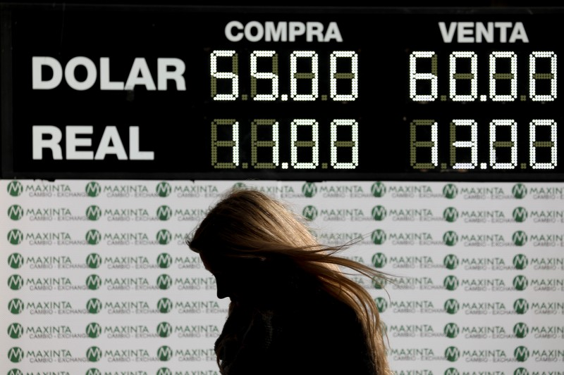 A woman walks past a currency exchange board in Buenos Aires on Aug. 12.