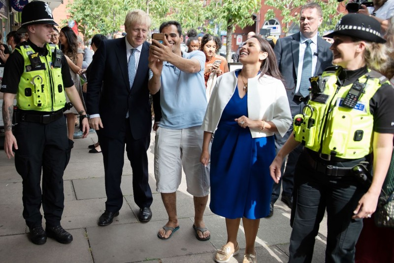 Britain's Prime Minister Boris Johnson (center) greets members of the public on a walkabout with Britain's Home Secretary Priti Patel (2nd from right) and members of West Midlands Police in Birmingham, England on July 26.