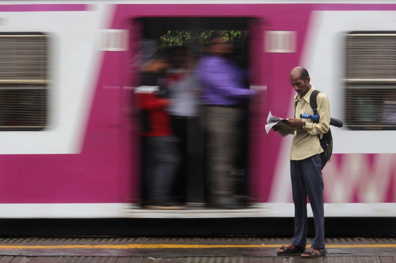 A man reads a newspaper on a railway platform in Mumbai on July 24.