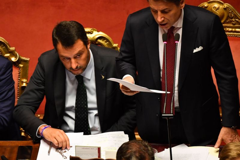 Italian Deputy Prime Minister and Interior Minister Matteo Salvini (L) holds a rosary as Italian Prime Minister Giuseppe Conte (R) delivers a speech in the Italian Senate in Rome, on Aug. 20.