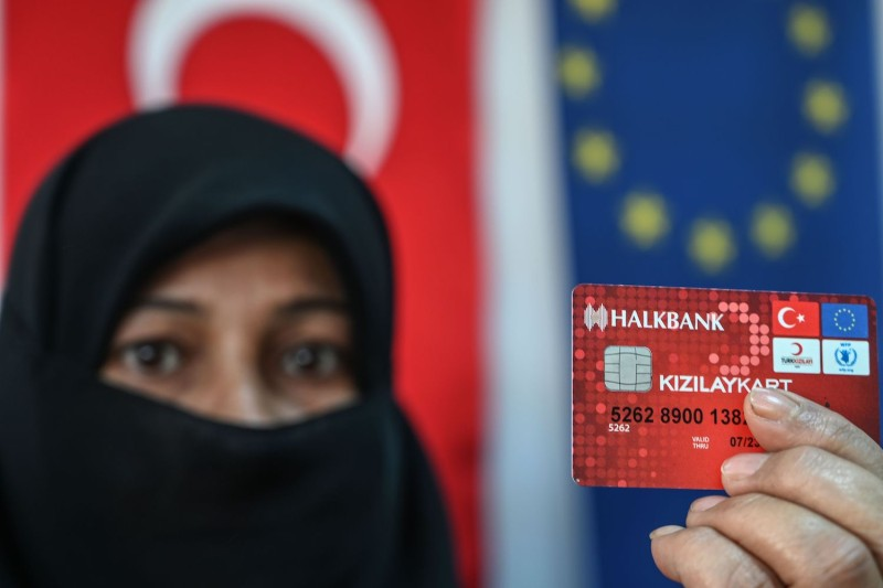 A Syrian woman shows her bank card, part of the Conditional Cash Transfer for Education program funded by the European Union and managed by UNICEF, the Red Cross, and Turkish authorities, in Adana, Turkey, on March 18.