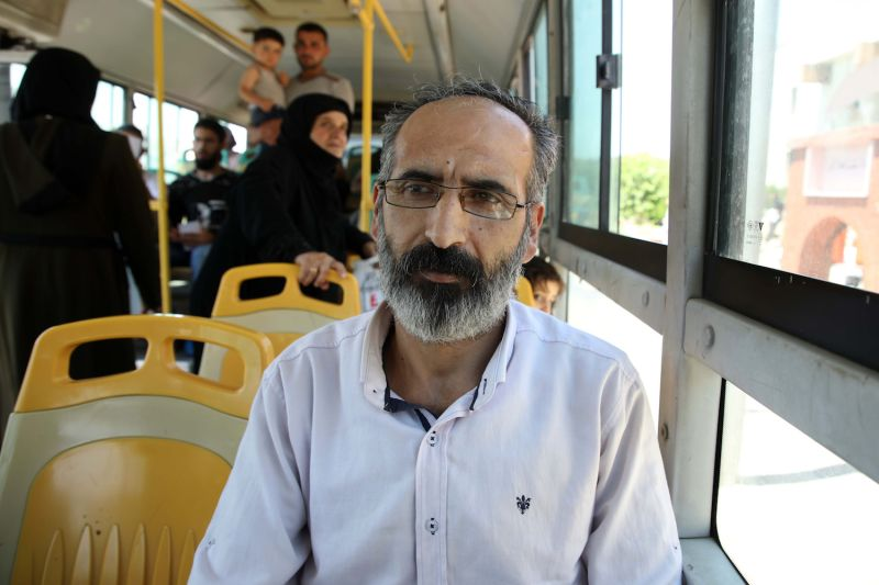 Syrian refugee Nidal Hussein Hussein, one of those suddenly deported from Turkey, rides in a bus transporting him through the Bab al-Hawa crossing between Turkey and Syria's northwestern Idlib province, as he re-enters Syria on July 24.