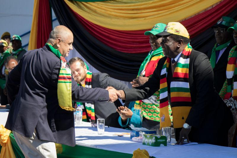 Zimbabwean President Emmerson Mnangagwa shakes hands after addressing a meeting attended by white Zimbabwean farmers and businessmen on July 21, 2018 in Harare.