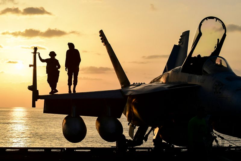 Sailors watch the sunset atop an F/A-18E Super Hornet on the aircraft carrier USS Theodore Roosevelt in the 5th Fleet area of operations on March 23, 2018.