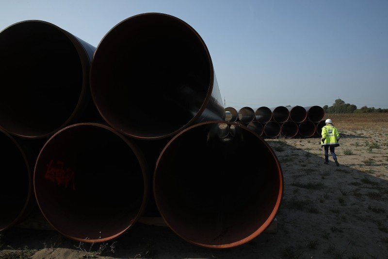 An employee of GASCADE Gastransport GmbH walks among sections of steel pipe stacked ahead of construction of the Eugal natural gas pipeline at Rietzneuendorf-Staakow on August 29, 2018 near Golssen, Germany.