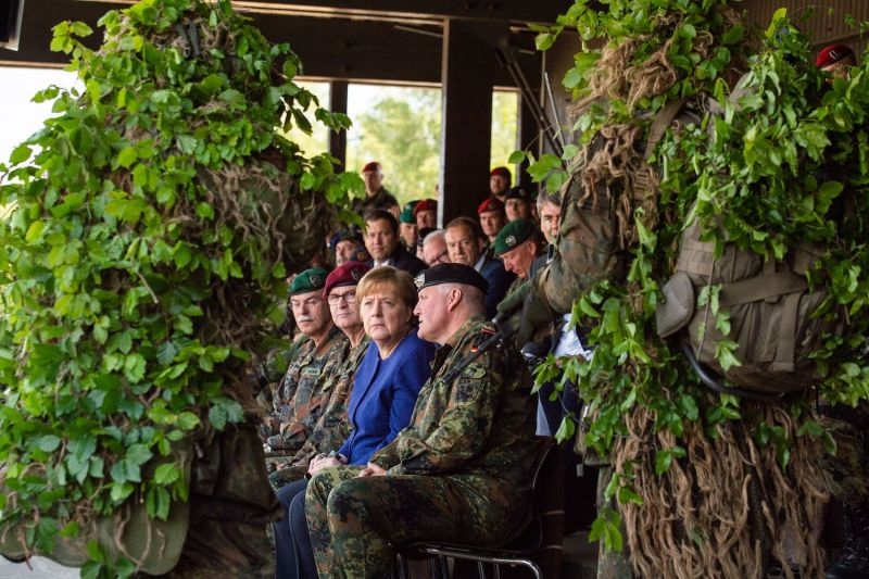 German chancellor Angela Merkel talks to brigadier-general Ullrich Spannuth while watching a NATO tank unit at the military training area in Munster, northern Germany, on May 20, 2019.