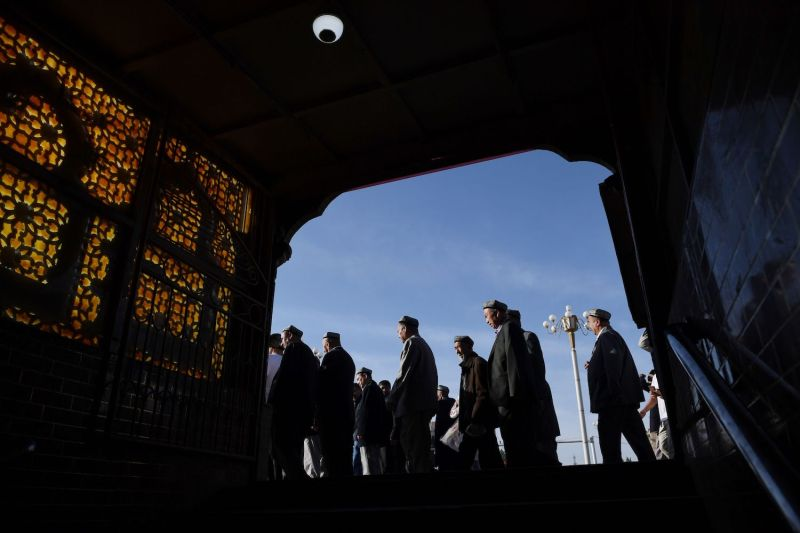 Uighur men make their way past a subway entrance after marking the end of Ramadan at the Id Kah mosque in Kashgar, in China's western Xinjiang region early on June 5.