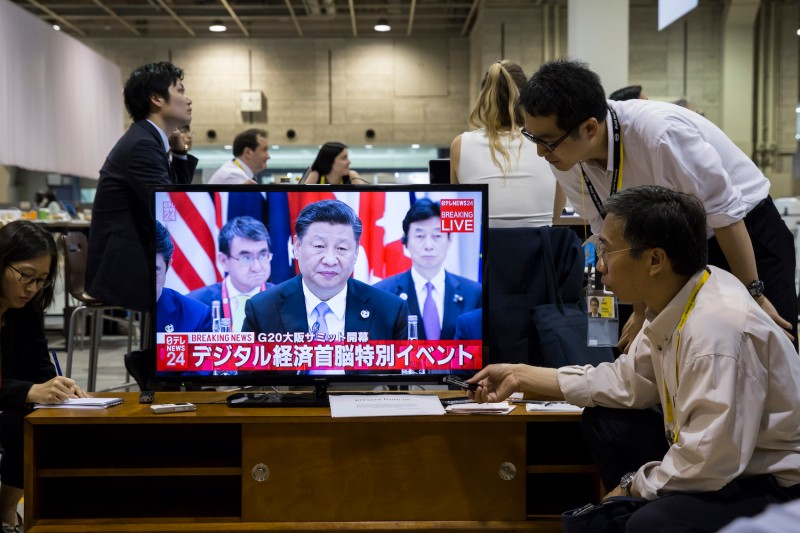 Journalists watch a live broadcast of Chinese President Xi Jinping speaking during the first session of the G20 summit in Osaka, Japan, on June 28.