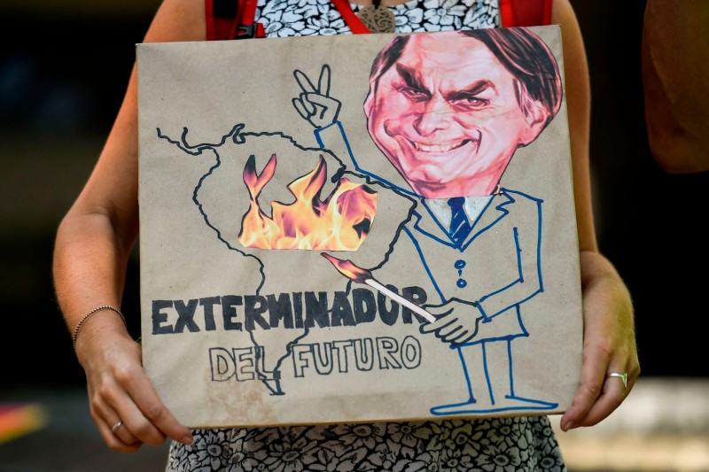 "An activist holds a sign depicting Brazilian President Jair Bolsonaro with the slogan ""Exterminator of the Future,"" during a protest about the fires in the Amazon rainforest in Cali, Colombia, on Aug. 23."