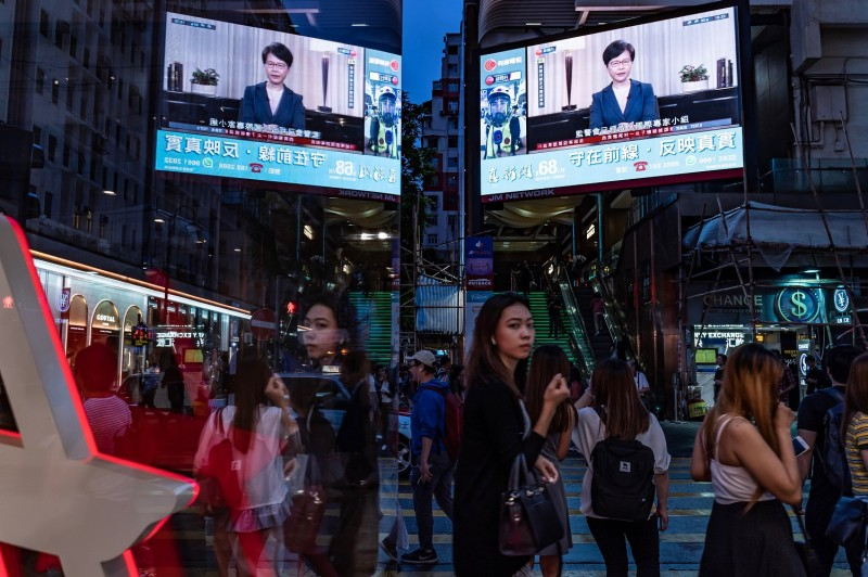 Pedestrians walk past a big screen television replaying Hong Kong Chief Executive Carrie Lam announcing the formal withdrawal of the extradition bill on September 4, 2019 in Hong Kong, China.