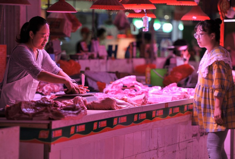 A customer shops for pork at a market in Beijing on September 5.