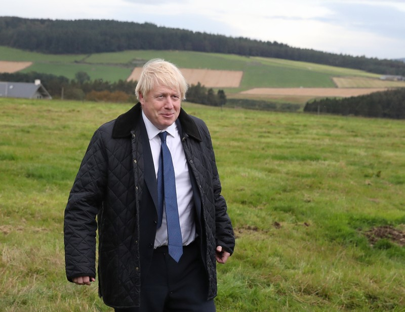 British Prime Minister Boris Johnson walks across a field near Aberdeen, Scotland, on September 6.