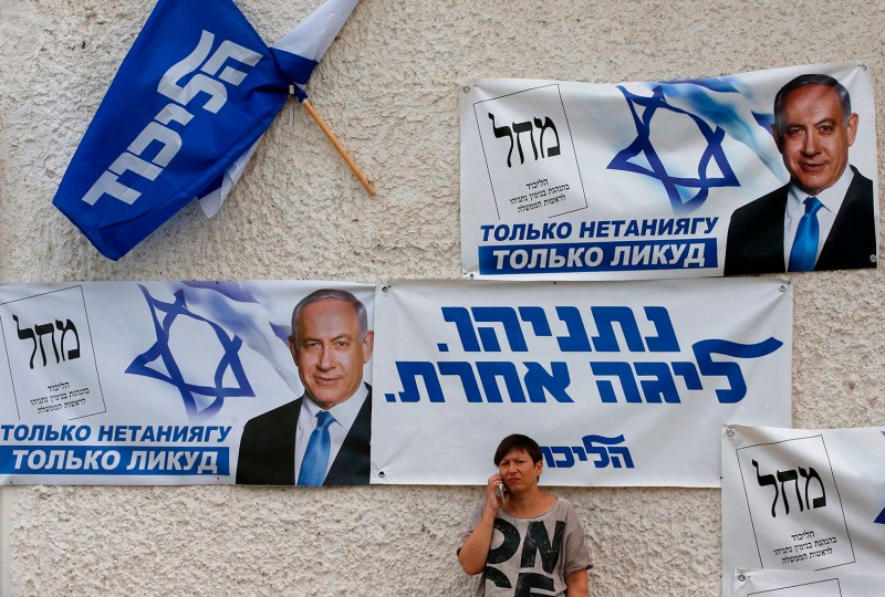 A woman talks on her mobile phone below banners for the Likud party show of Beersheva, Israel, on Sept. 15.