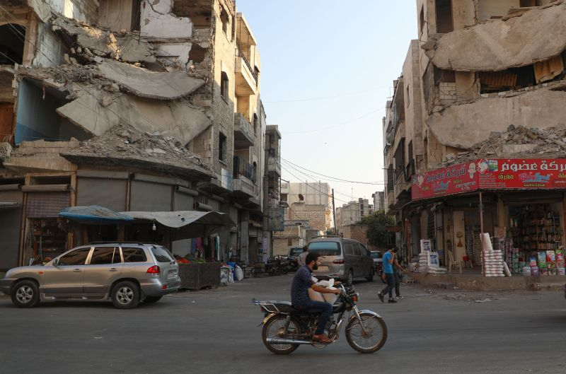People walk near heavily damaged buildings in the rebel-held city of Idlib in northwestern Syria on Sept. 16.