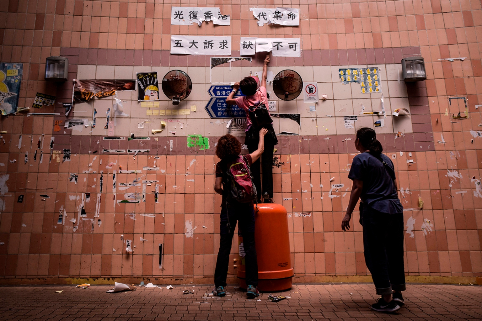 "Locals remove banners, posters, and sticky notes from a ""Lennon Wall,"" one of many which appeared during the recent pro-democracy protests, in an underground walkway in the Aberdeen area of Hong Kong on Sept. 21. RICHARD A. BROOKS/AFP/Getty Images"