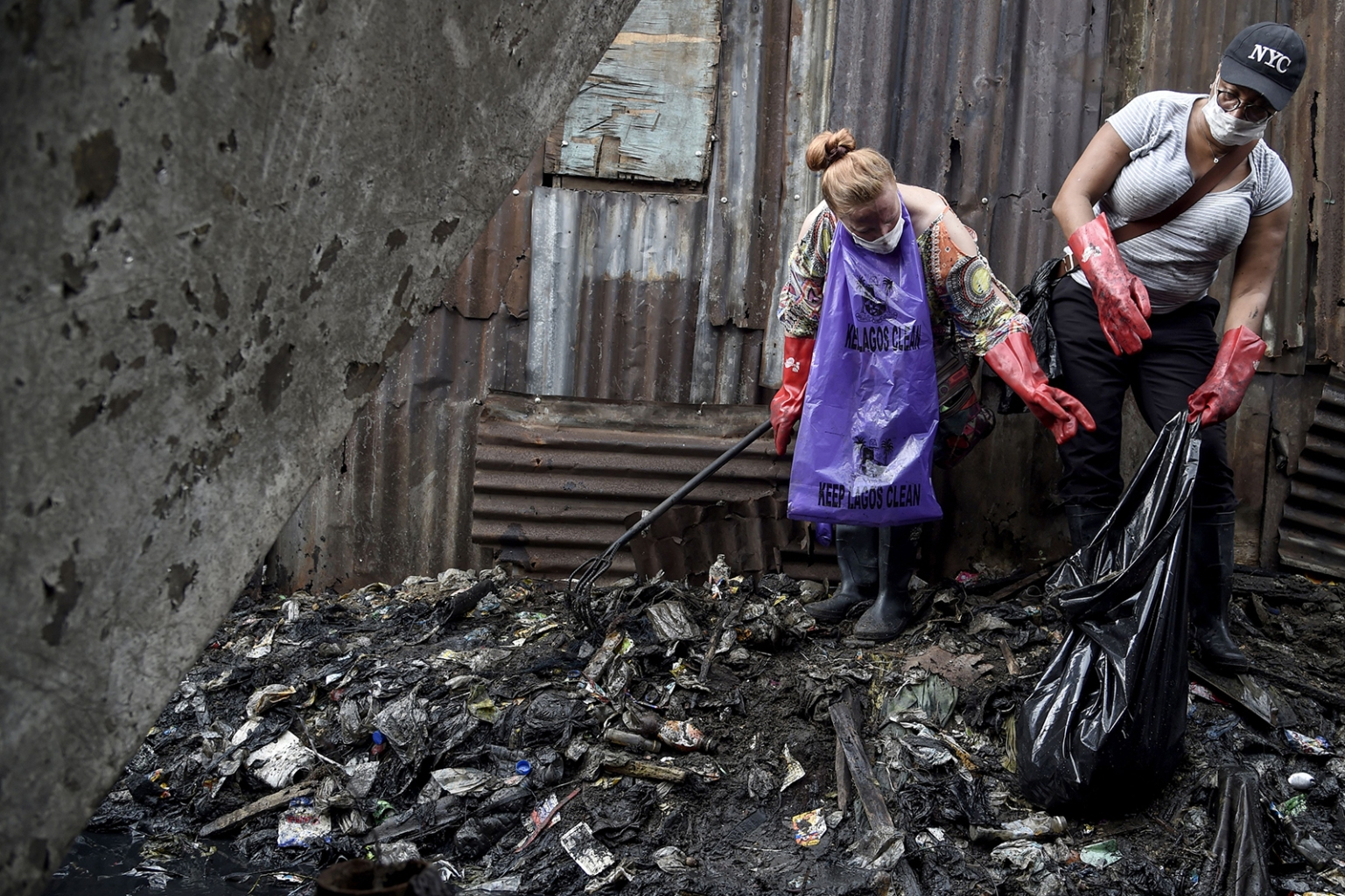 Volunteers for Mondo4Africa, a non-governmental organization, work to clean up waste at Makoko, the largest community slum settlement at the lagoon waterfront in Lagos, Nigeria, on Sept. 21. PIUS UTOMI EKPEI/AFP/Getty Images